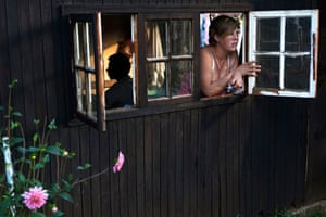 A woman looks out the window of her one-room hut at a squatter camp for poor white South Africans at Coronation Park in Krugersdorp; many have fallen on hard times due to a shift in racial hiring practices and the recent global economic crisis.