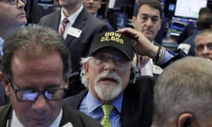 """Trader Peter Tuchman, centre, wears a """"Dow 22,000"""" hat on August 2, 2017."""