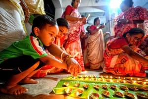 Hindu devotees light Diyas (clay lamps) in front of the idol of Lord Durga during the Sandhi Puja Ritual of Durga Ashtami.