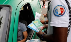 Two police officers give brochures to a motorist explaining the new measures that will ban old cars from Paris.