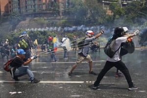 Anti-government protesters work together to aim a giant slingshot at security forces blocking their march from reaching the Supreme Court in Caracas, Venezuela,on 10 May during protests over high crime, sky-high inflation and shortages of food and medicine