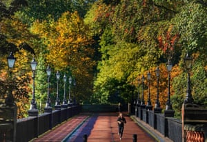 Newcastle, UKA jogger runs over the Armstrong Bridge surrounded by autumn colours