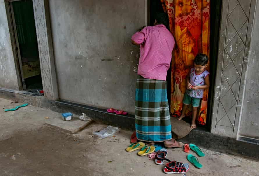 A child waits outside their mother's room while she works.