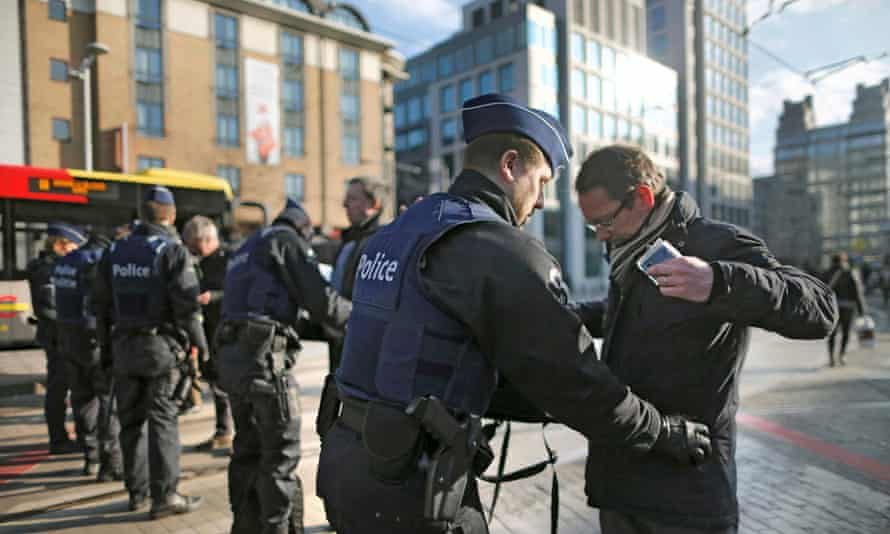 A man is searched in Brussels following the bomb attacks.