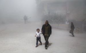 A man and girl flee following a reported government airstrike on the rebel-controlled town of Hamouria.