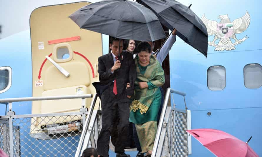 Joko Widodo and his wife Iriana battle against strong wind and rain on their arrival at Sydney on Saturday.