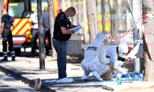 Forensic police examine a bus shelter in Marseille.