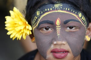 Bali, Indonesia. A young villager takes part in the Hindu ritual of Grebeg in Tegalalang, Gianyar Regency. Participants paint their faces and bodies and parade around their village to ward off evil spirits