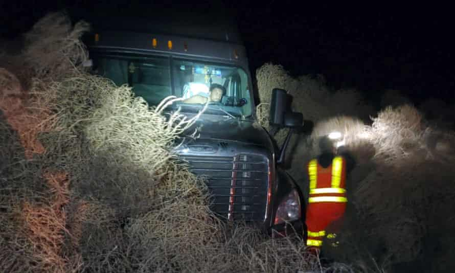 A truck trapped by a pile of tumbleweeds .