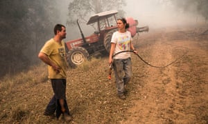Ian Wheeler and April Walsh fight a fire on their neighbour's property in Killabakh, NSW
