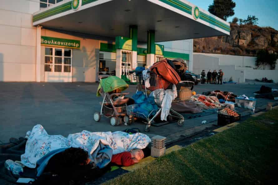 Homeless refugees sleep at a fuel station, Moria