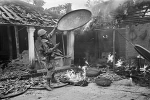 A 1st Cavalry Division soldier throws a rice basket onto the flames as his unit sweeps through a village near Tam Ky, 350 miles northeast of Saigon, October 27, 1967