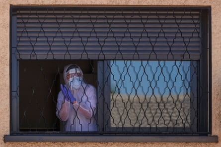 A member of the Military Emergencies Unit appears at a window during a disinfection in the Getafe suburb of Madrid on 25 March.