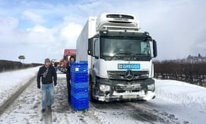 A Greggs delivery driver hands out free cakes and pastries to snowed-in drivers in March last year.