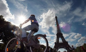 A man rides a Vélib' bicycle near the Eiffel Tower.
