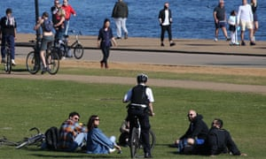 A police officer speaks to people relaxing by the Serpentine in Hyde Park, London, durng the lockdown in April.