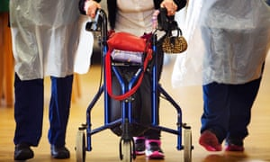 Carers and a resident using a walking frame