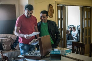 Taraya, Lebanon - Chamran Hamieh [left], Hamza Akel Hamieh's son, goes through his father's collection of images from the civil war, stored in old suitcases in his home in the the Bekaa Valley. Hamza Akel became a legend in the Middle East after hijacking six planes between 1979 and 1982 -- a record to this day -- to draw the world's attention to the kidnapping of Musa Sadr, his religious leader. One of the hijackings, in 1981, was among the longest in aviation history.