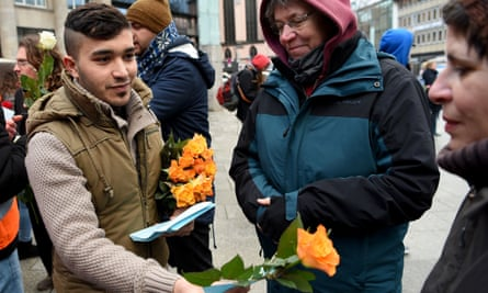 Refugees from Syria present flowers to passers-by in Cologne. Unease is growing among German MPs over the nation's ability to absorb millions of newcomers.