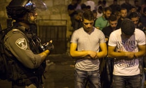 An Israeli border policeman holds a stun grenade in his hand while Palestinian teenagers pray in the street near an entrance to the al Aqsa mosque in Jerusalem.