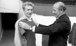 Manchester United manager Matt Busby (r) holds a United shirt against his new signing, Denis Law (l), who cost £115,000 from Torino