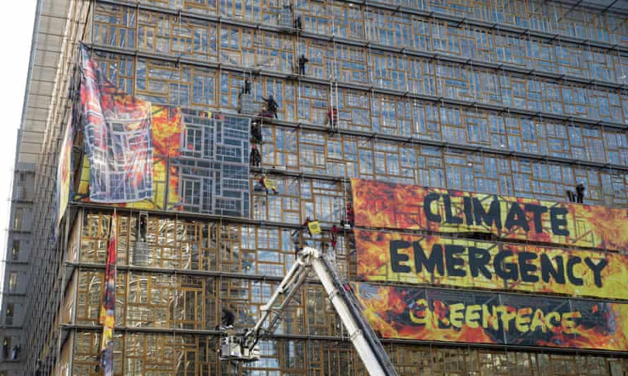 Firefighters and police remove the Greenpeace placard from the Europa building in Brussels, Belgium.