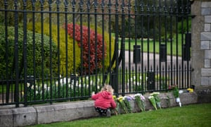A young girl adds her flowers to the floral tributes outside Windsor Castle.