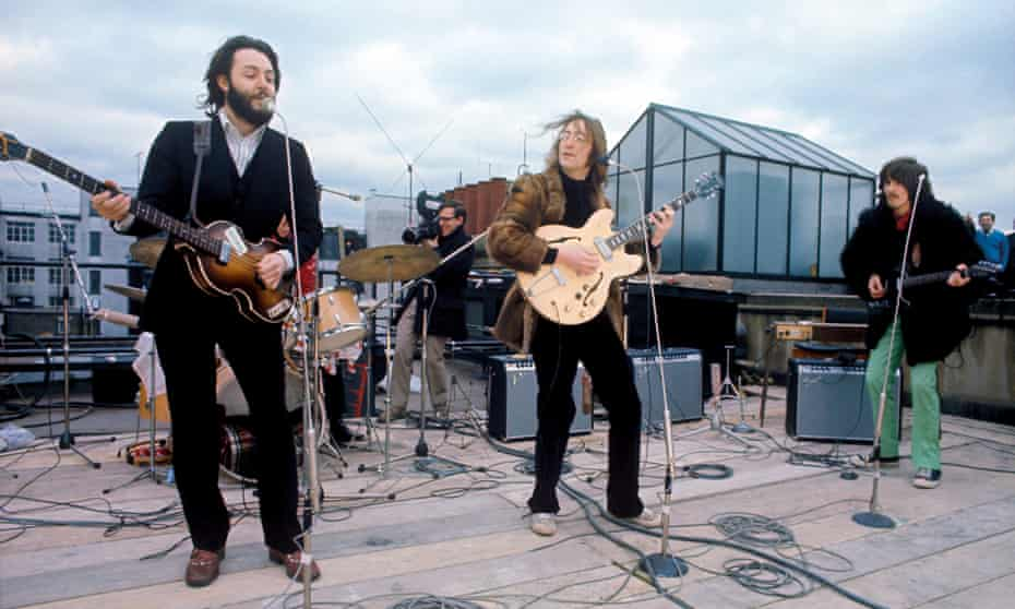 The Beatles play on the rooftop of their Apple Corps HQ.