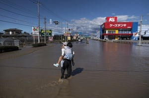 A woman carries her daughter through floodwater following the passage of Typhoon Hagibis on October 13, 2019 in Sano, Tochigi.