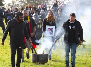 Family members, including Tanya's daughter Apryl Watson (centre), march to the Coroners Court after smoking ceremony in Kings Domain Park