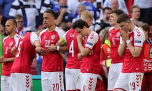 Denmark players provide a shield for Christian Eriksen as he receives medical treatment on the pitch.