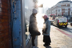 Two people wait outside a public laundry on the northern fringe of the Square Mile