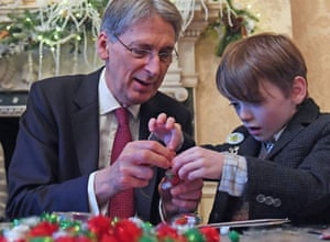 British Chancellor of the Exchequer Philip Hammond making Christmas decoration with Spike Coates during his Christmas party last week.