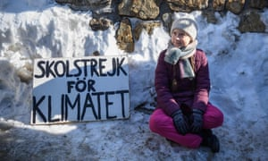 """Swedish climate activist Greta Thunberg sits next to a placard reading """"school strike for climate""""."""