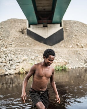 Ibrahim, 17, swims in the river beneath new tracks being built by a Turkish construction company in Awash National Park.