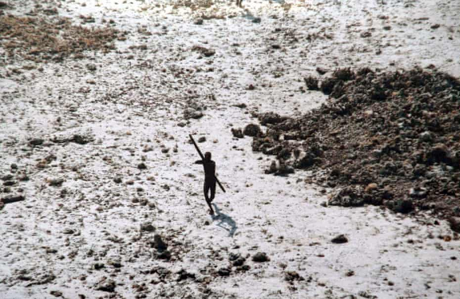 In this handout photo provided by the Indian Coast Guard and Survival International and taken in 2004, a man with the Sentinelese tribe aims his bow and arrow at an Indian Coast Guard helicopter.