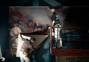 Workers hang a mural depicting the Battle of Bunker Hill as preparations for opening continue at the Museum of the American Revolution in Philadelphia.