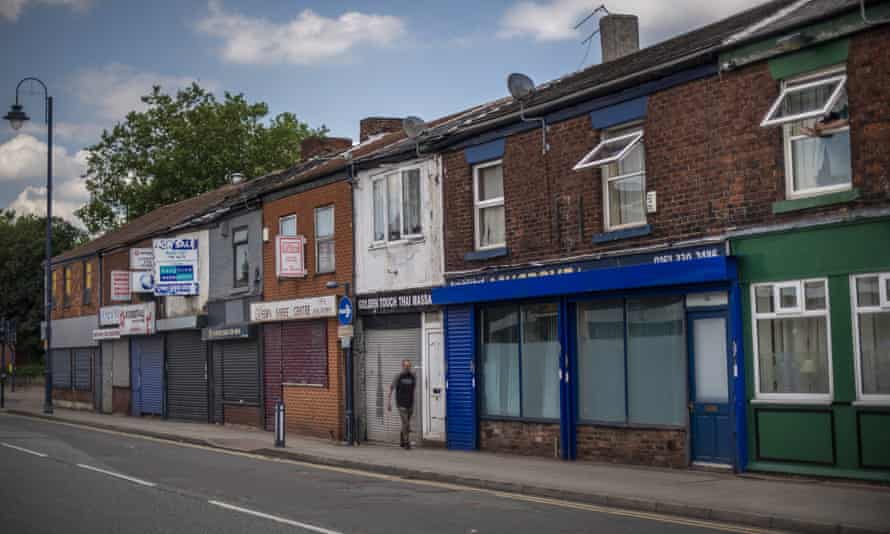 A man walks past closed shops in Ashton-Under-Lyne in June 2020 in Manchester.