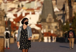 A young woman wearing a face mask walks across the medieval Charles Bridge in Prague, on Friday