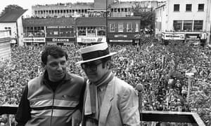 Watford Football Club Chairman Elton John wearing the club scarf with team manager Graham Taylor on a balcony overlooking a crowd of well wishers.