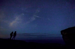 A couple watch meteors along the Milky Way in Comillas, Spain