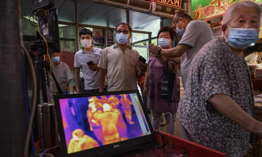 Shoppers have their temperature checked by thermal imaging at the entrance to a local market in Beijing.