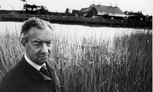 Benjamin Britten, wearing a shirt and tie and buttoned-up jacket, in long grass