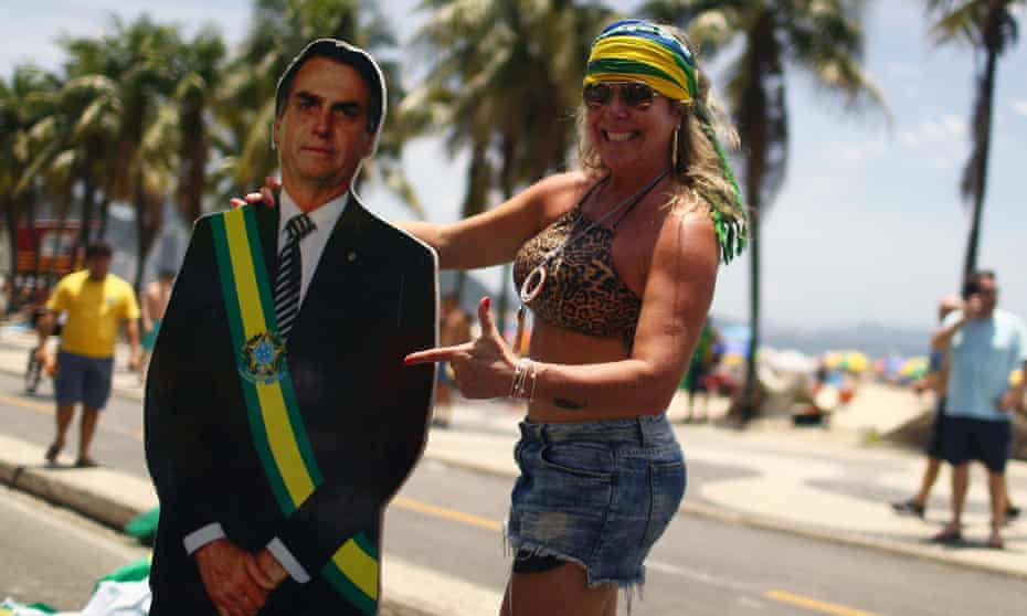 A demonstrator holds a cardboard cutout depicting Brazilian President Jair Bolsonaro in Rio de Janeiro, Brazil, on 8 December .