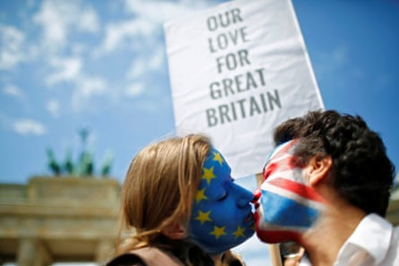 Two activists with the EU flag and Union Jack painted on their faces kiss each other in front of Brandenburg Gate to protest against Brexit in Berlin, June 2016