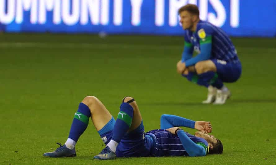 Kieffer Moore is dejected after Wigan drew 1-1 with Fulham on the last day of the season, meaning the points deduction would lead to relegation