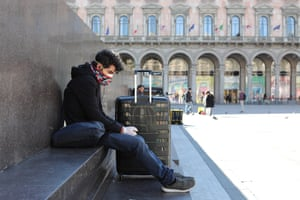 A tourist wears a protective mask and gloves as he sits with his luggage in the Duomo Square on Friday in Milan.