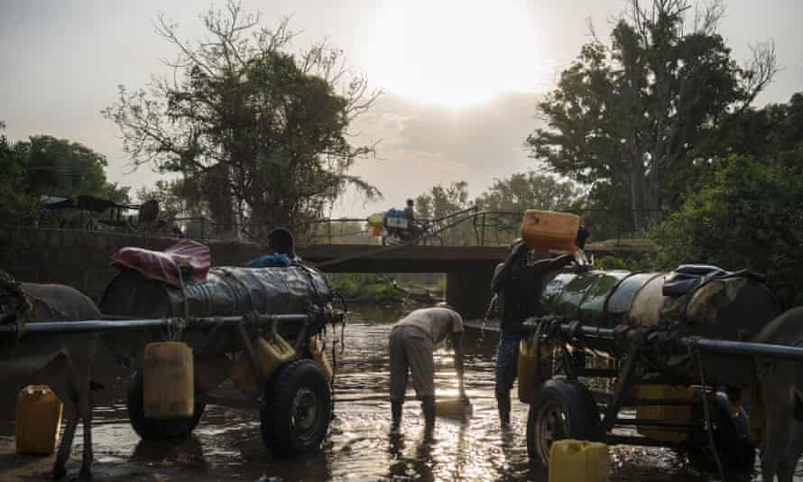 Men fill water tanks from a river in Sudan