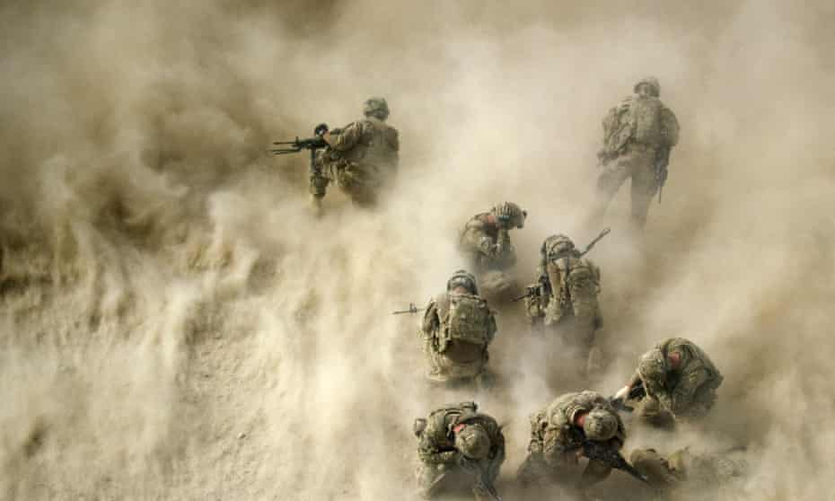 American soldiers in Afghanistan shield themselves from dust whipped up by a helicopter's rotor blades