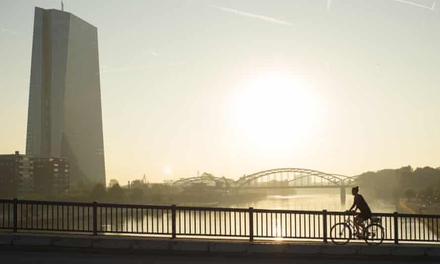A cyclist rides across a bridge as the skyscraper headquarters of the European Central Bank.